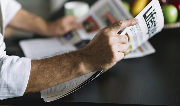 man-s-hand-holding-newspaper_23-2147901151